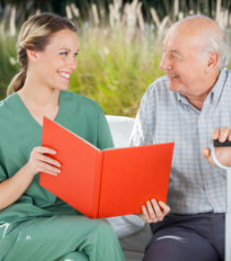 caregiver and elder man smiling while reading the book