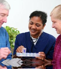 nurse showing medicines to the elder couple