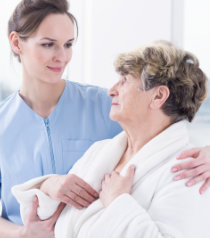 caregiver trying to assist the elder woman