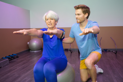 caregiver assisting the elder lady in exercise